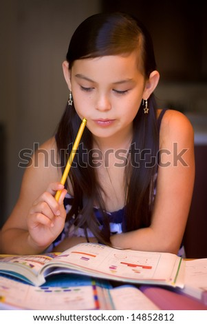 Girl working on a homework with books in front of her