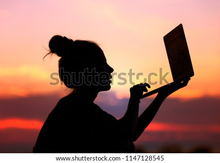 girl working on laptop during beautiful sunset outside. freelance woman typing on computer keyboard sitting outdoors in the evening. wireless internet connection allowing to work everywhere.
