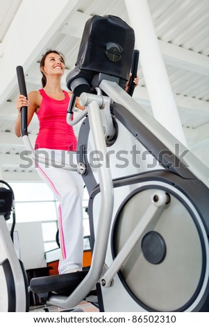 Girl working out at the gym indoors - stock photo