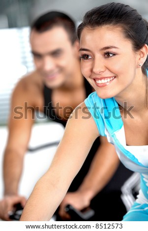girl working out in a gym with a guy in the background
