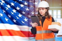 Girl works in USA. Customs. Girl in working uniform on the background of USA flag. American works at customs. US Customs Officer. Girl holds a tablet and boxes. Woman registering parcels using tablet
