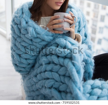 girl wrapped in a blue blanket knit. cosy sitting near the window. the girl with a warm Cup in hands