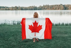 Girl wrapped in large Canadian flag by Muskoka lake in nature. Canada Day celebration outdoor. Kid in large Canadian flag celebrating national Canada Day on 1 of July.