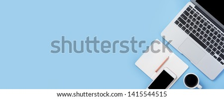 Photo of Girl write on open white book or accounting on a minimal clean light blue desk with laptop and accessories, copy space, flat lay, top view, mock up