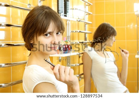 Girl writes a love letter on a mirror with eyeliner - stock photo