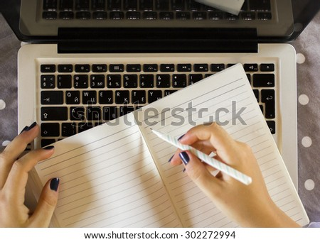 girl writes in a notebook, with laptop