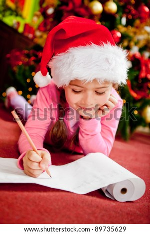 Girl writing a Christmas wish list for Santa