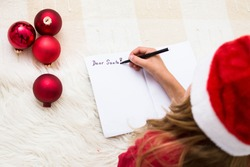 Girl writing letter for Santa Claus. Child in red santa hat lying on bed and writing christmas letter. Christmas celebration concept. Top view over shoulder, coyp space.