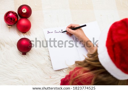 Photo of  Girl writing letter for Santa Claus. Child in red santa hat lying on bed and writing christmas letter. Christmas celebration concept. Top view over shoulder, coyp space.
