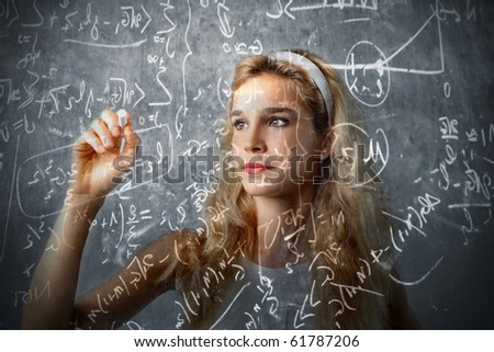 Girl writing some formulas on a blackboard