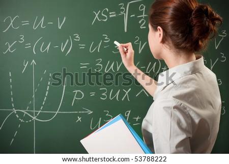 girl writing the mathematical formulas on a chalkboard - stock photo