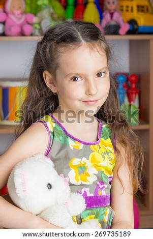 Girl 6 years brunette in colorful dress sitting on a chair holding a stuffed toy white bear