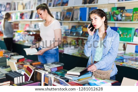 Girl 10-15 years old is choosing book while calling in bookstore.
