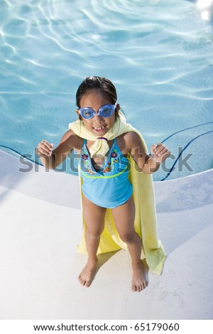 Girl, 7 years, playing by swimming pool in pretend superhero costume