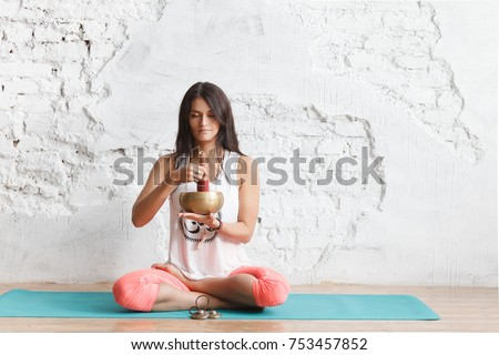 girl  yogi plays on the Tibetan singing bowl. Young woman meditating in a yoga on white background, Yoga and healthy lifestyle concept #753457852