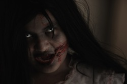 Girl zombie in blood. Closeup face and eyes of Asian Woman ghost with blood. Horror creepy scary fear in a dark house. Hair covering the face, Halloween festival concept