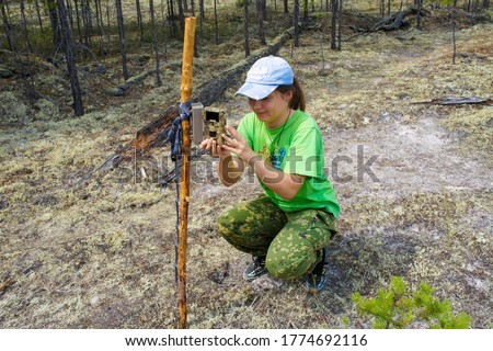 Girl zoologist sets camera trap for observing wild animals in forest to collect scientific data. Environmental protection, monitoring of rare and endangered animal species, ecology World Wildlife Day Zdjęcia stock ©