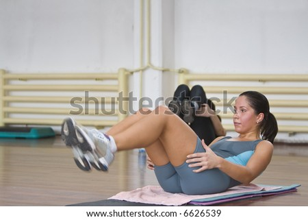 Girldoing aerobics floor exercises in a fitness gym.