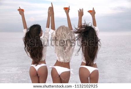 Girlfriend. Happy three female friends in sexy bikini having fun on white beach at sunset. Group of slim ladies cheering with glass of aperol spritz cocktail. Women Enjoying life with drinks.