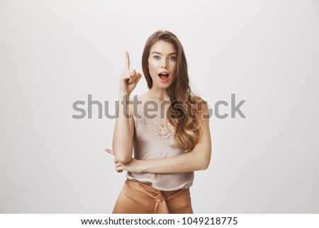 Girlfriend has idea to solve problem. Portrait of clever attractive european female raising index finger in eureka gesture, saying her suggestion to friend, discussing new concepts and solutions