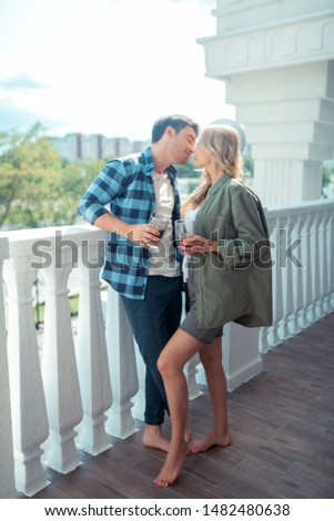 Girlfriend kissing. Appealing girlfriend kissing her handsome man while drinking coffee together #1482480638