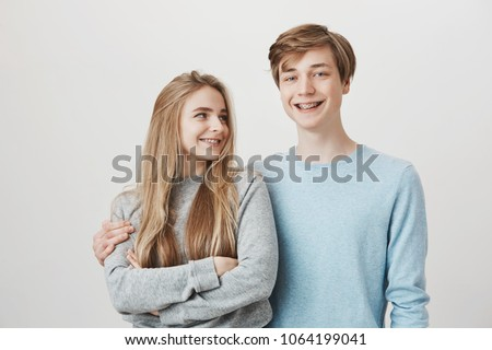 Girlfriend knows boyfriend prepared something for anniversary. Portrait of two friendly caring siblings, hugging and smiling broadly, wearing shiny braces. Girl looking at guy who dare to cuddle her