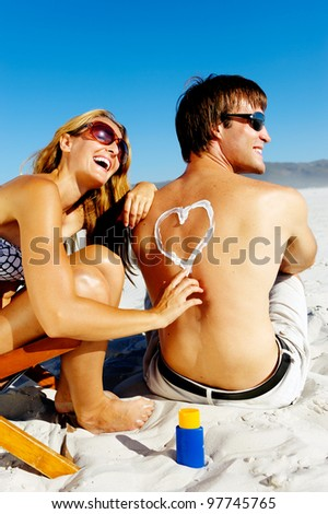 Girlfriend playfully draws a heart on her boyfriends back with spf suncream to protect him from the harsh sun while on their tropical summer beach vacation
