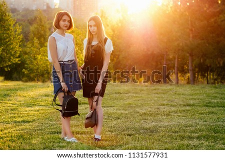 girlfriend schoolgirls stylish dress and bags backpack posing in forest the lights of a sun at sunset #1131577931
