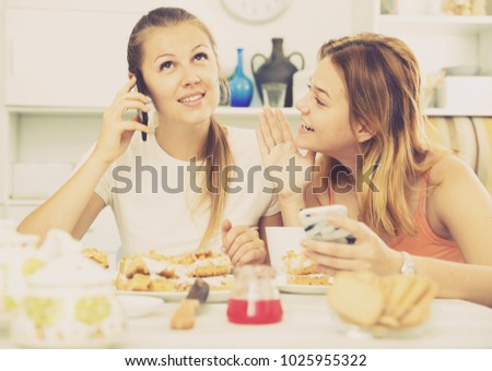 Girlfriends are playfull talking by phone at home. #1025955322