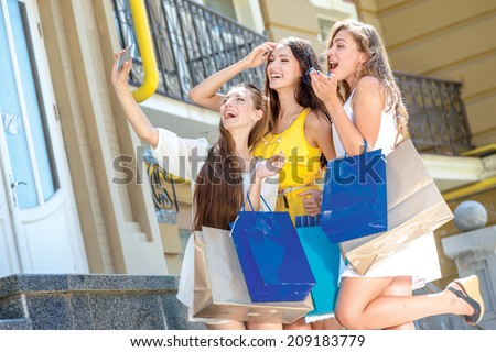 Girlfriends do selfie on a cell phone. Girls holding shopping bags and walk around the shops. Smiling girl photographed on a cell phone. Girlfriends posing in front of the camera