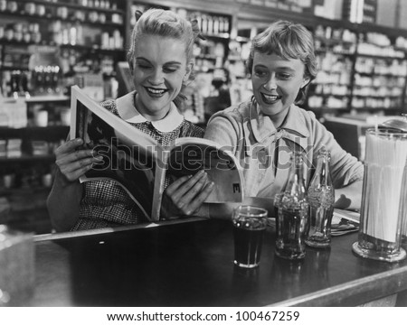 girlfriends looking at magazine ...