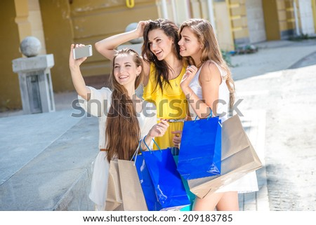 Girlfriends make selfie on a cell phone. Girls holding shopping bags and walk around the shops. Smiling girl photographed on a cell phone.