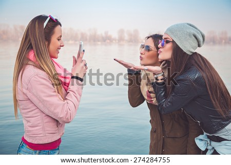 Girlfriends taking a photo of them sending kiss
