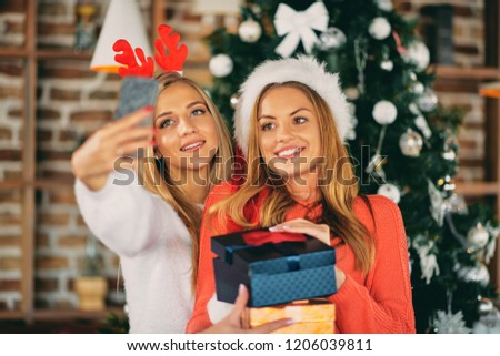 Girlfriends taking selfie and holding gifts while standing in front of Christmas tree. Christmas and winter holidays concept.