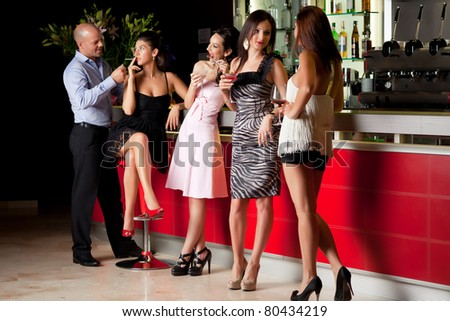 girlfriends talking at the bar, man lighting girl cigarette