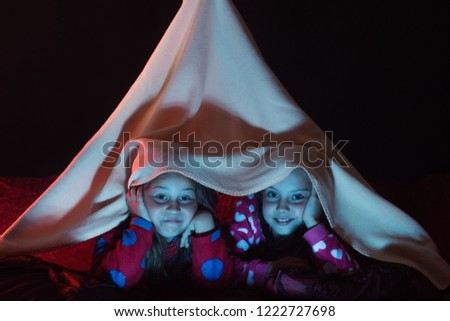 Girls and pajama party concept. Children with smiling faces lie under pink  blanket tent. 5259f737c