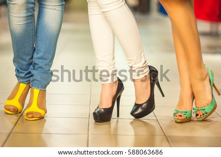 Girls and shopping, slender legs of a girl with shopping bags in a boutique or mall