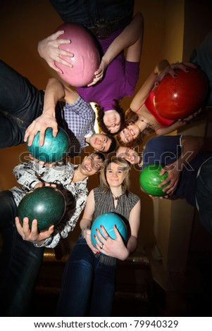 Girls and youths stand in close circle and everybody gets on  hip  ball for bowling - stock photo