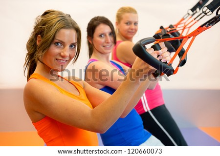 Girls are doing suspension training in the sports club