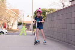 Girls are wearing safety helmets while scootering on the sidewalk of their LA city.