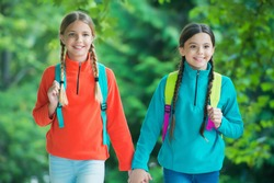 Girls backpackers friends fleece clothes backpacks forest background, family hike concept.