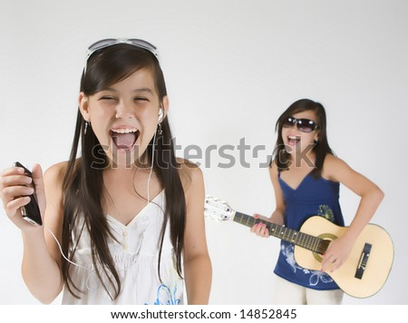 Girls band singing and playing on guitar