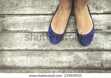Girls beautiful blue shoes over wooden deck.