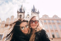 Girls, best friends are walking around Prague. Blonde and brunette enjoy traveling in Prague in the background Old Town Square. Closeup portrait.