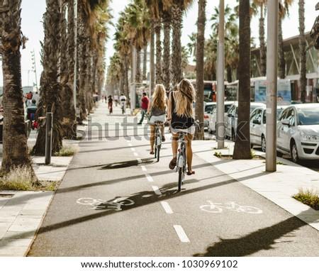 girls bike along the palm tree lane in Barcelona