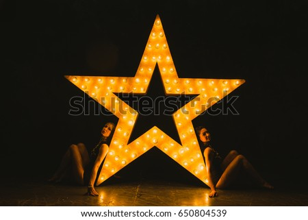 Girls dance against the backdrop of a glowing star #650804539