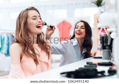 Girls do makeup in the showroom. Two beautiful girls have fun and smile. They are sitting in a bright room opposite the mirror.