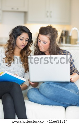 Girls doing homework with laptop and notepad on sofa in living room