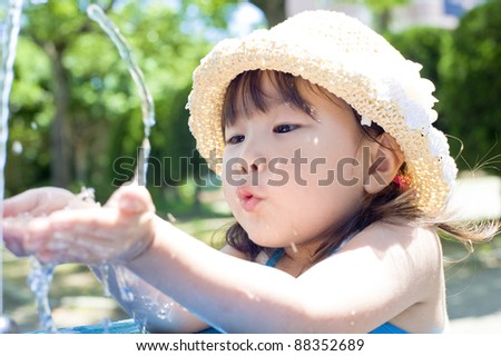 Girls drink tap water in the park - stock photo