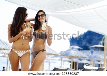 Girls drinking cocktails on beach in bikinis